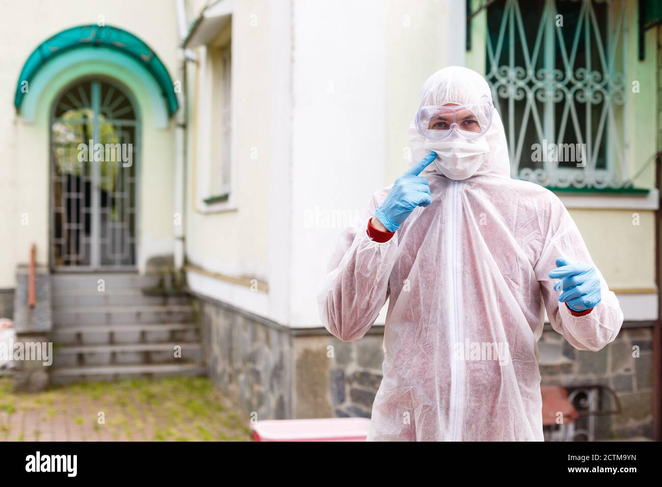 selective focus of smiling male scientist in protective mask and suit looking at camera outdoors Stock Photo