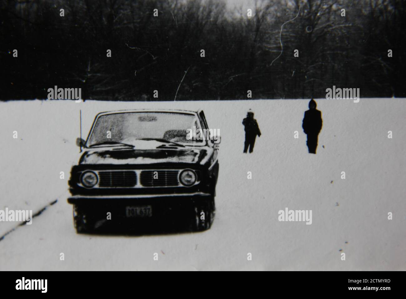 Fine 1970s vintage black and white photography of a car parked at the edge of the wilderness and two young kids walking around in the middle of the winter. Stock Photo