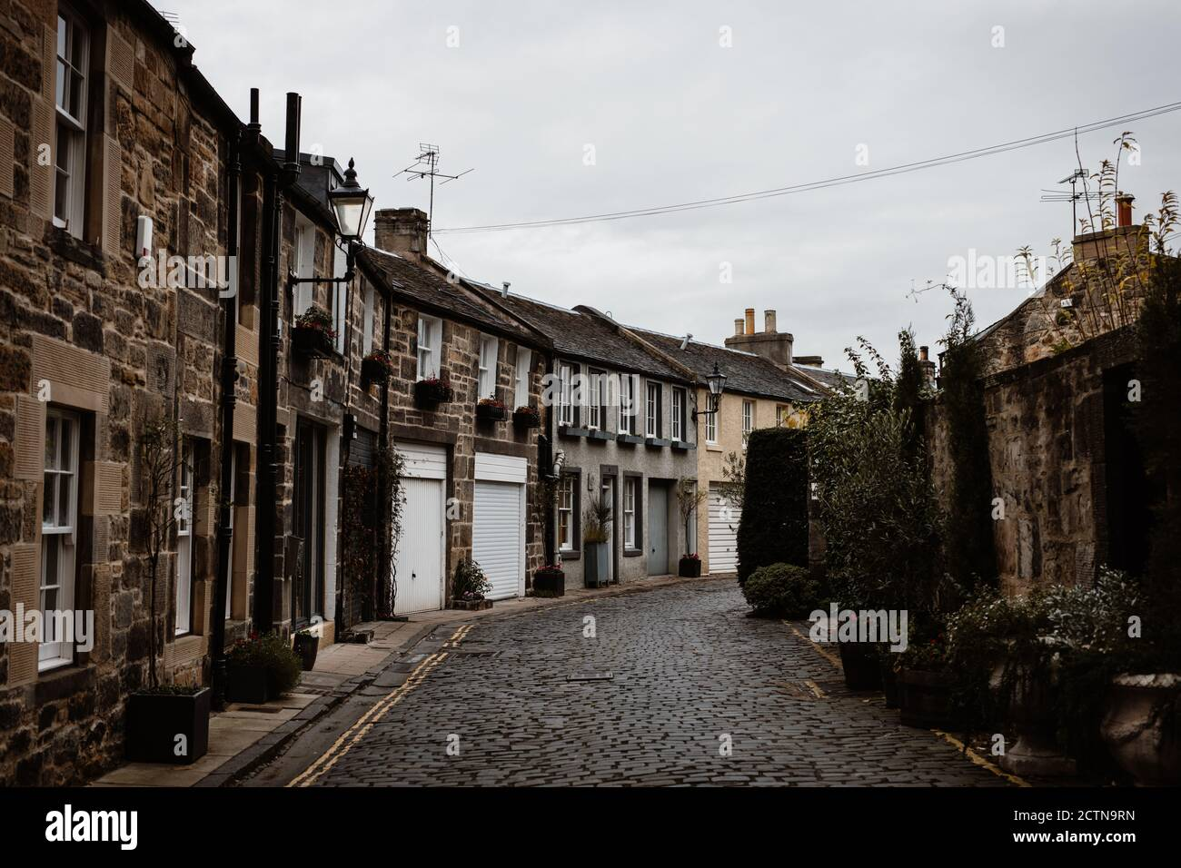 Perspective view of old narrow street with grunge residential buildings on background of gray sky in Scottish Highlands Stock Photo