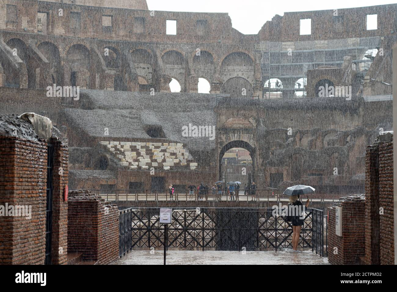 Rome, Italy. 24th September, 2020. Italy Weather: A woman shelters from heavy rain under an umbrella in the Roman Colloseum in Rome, Italy. Photo: Roger Garfield/Alamy Live News Stock Photo