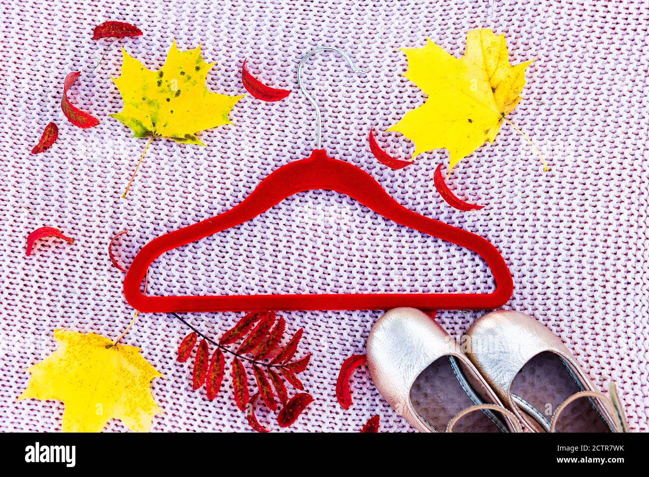 A clothes hanger and golden shoes lie among autumn colorful leaves Stock Photo