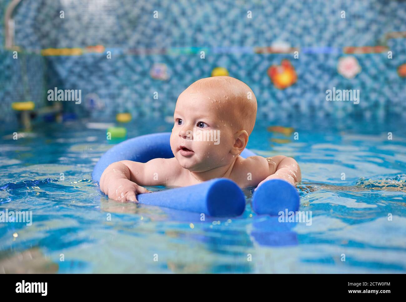 Cute child holding blue pool-noodle and gliding in crystal pool water while learning to swim. Adorable baby with water drops on face swimming in pool. Concept of childhood and safe swimming lessons. Stock Photo