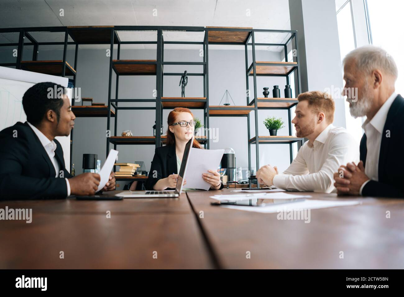 Motivated business woman leader holds meeting with employees at office desk, shooting from below. Stock Photo