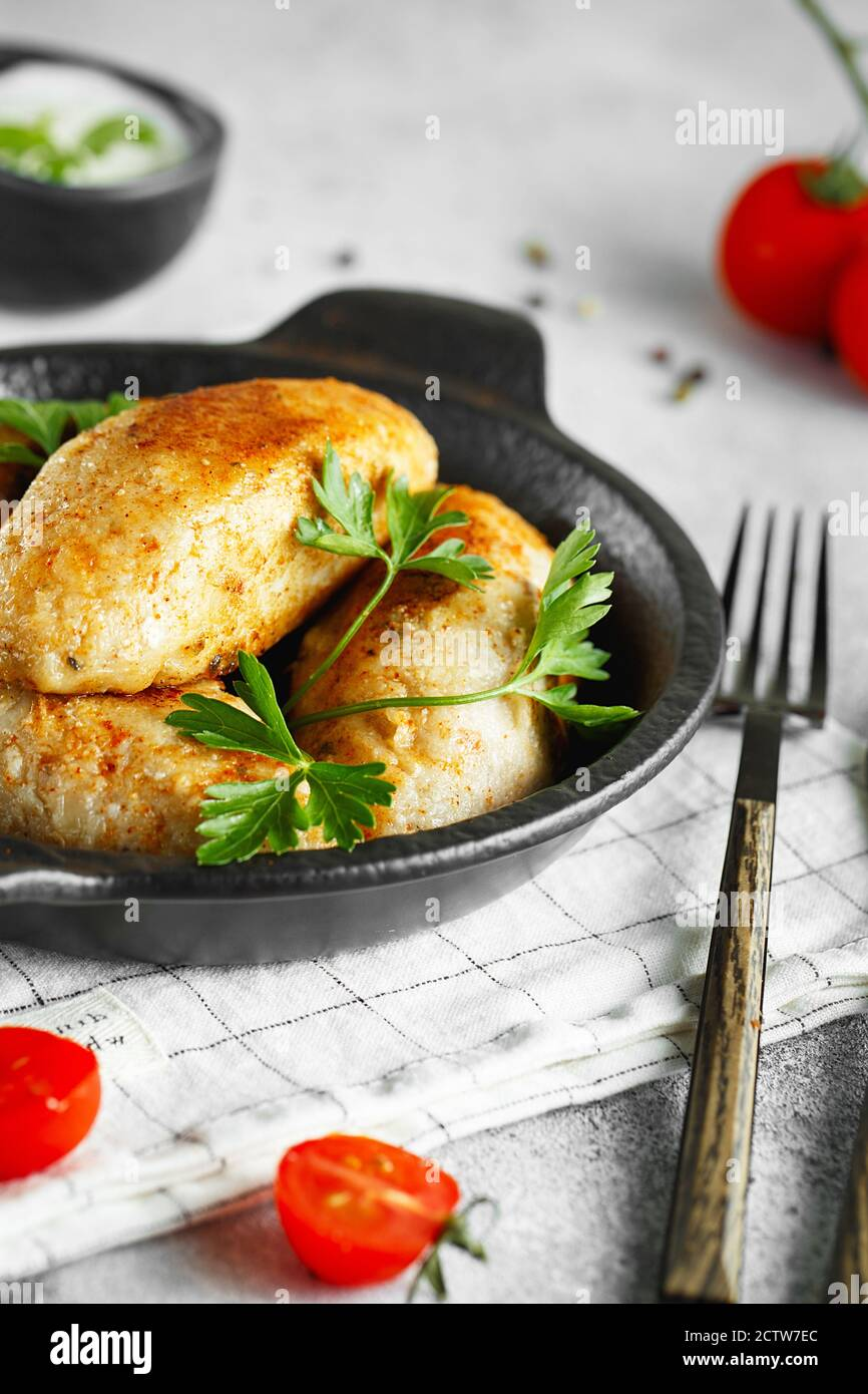 Delicious grilled beef or chicken meatballs. Meat or fish patties on the little frying pan served with parsley and tomatoes. Food photography. Stock Photo