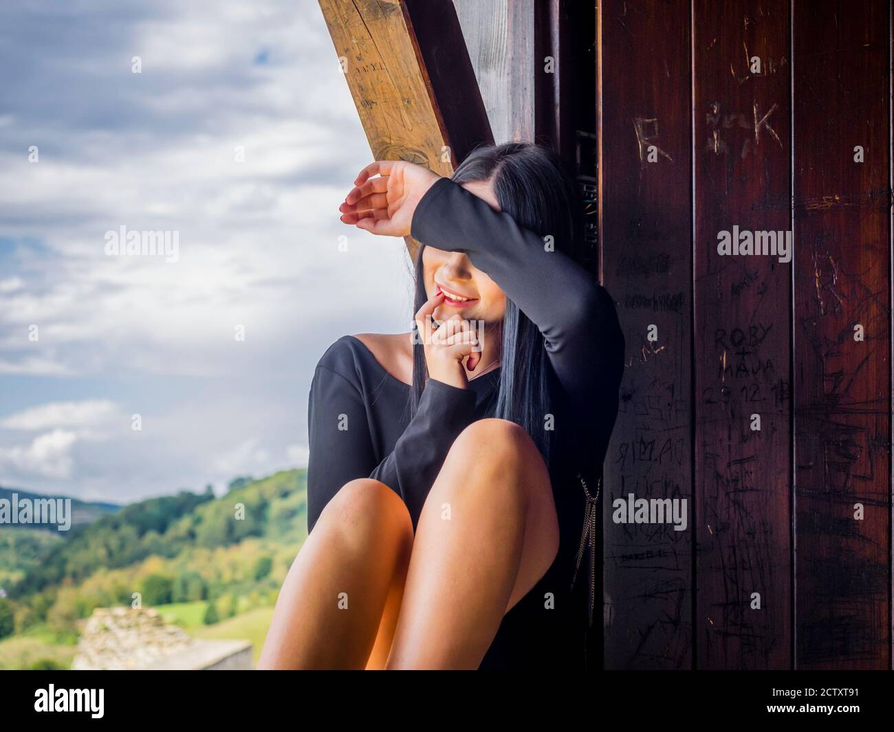 Teengirl sitting enjoying view daydreaming finger in mouth lips smiling happy looking away aside almost hidden identity hand cover covering face eyes Stock Photo