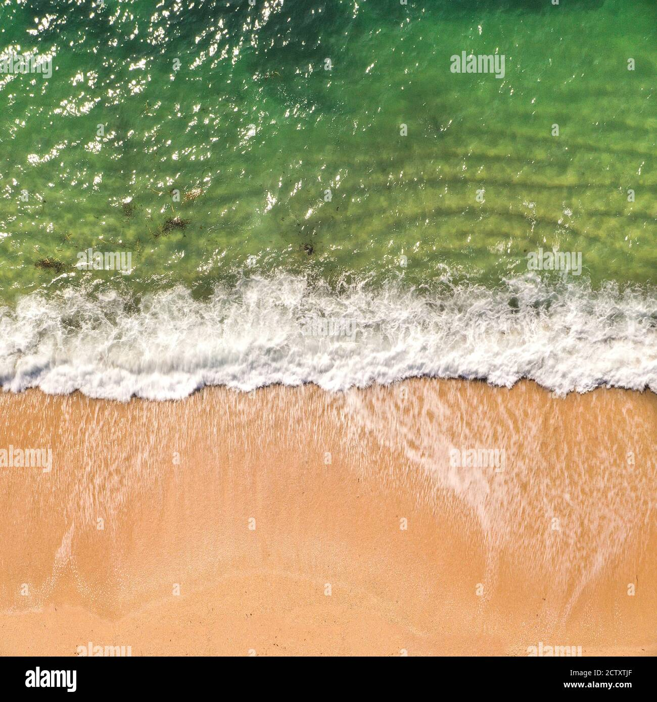 An aerial drone image looking down onto a sandy beach with white rolling waves and surf crashing onto a beach from an emerald green ocean in Cornwall, Stock Photo