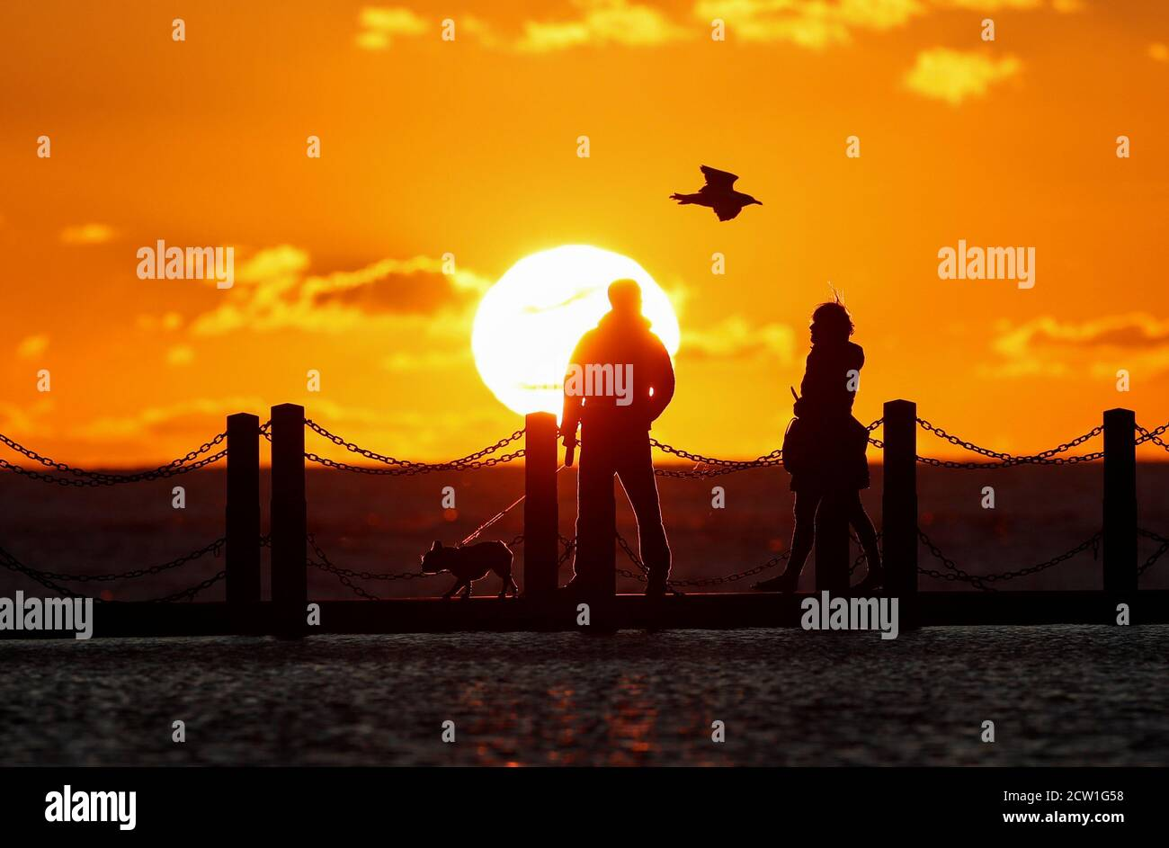 People are seen at Marine Lake as the sun sets over the Bristol Channel, Weston-super-Mare, Britain, September 26, 2020.  REUTERS/Peter Cziborra Stock Photo
