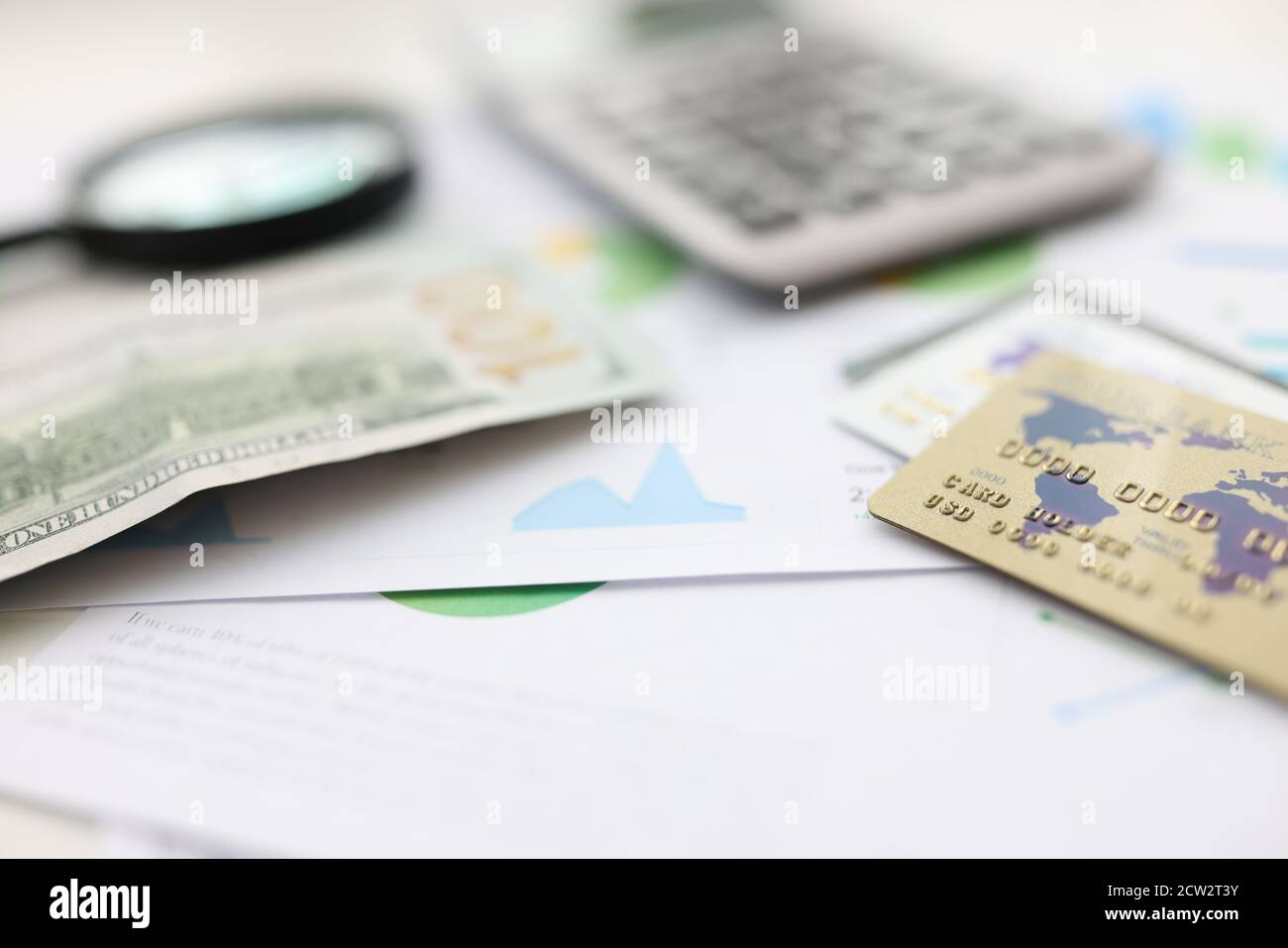 On table american dollars plastic cards and calculator and magnifying glass. Stock Photo