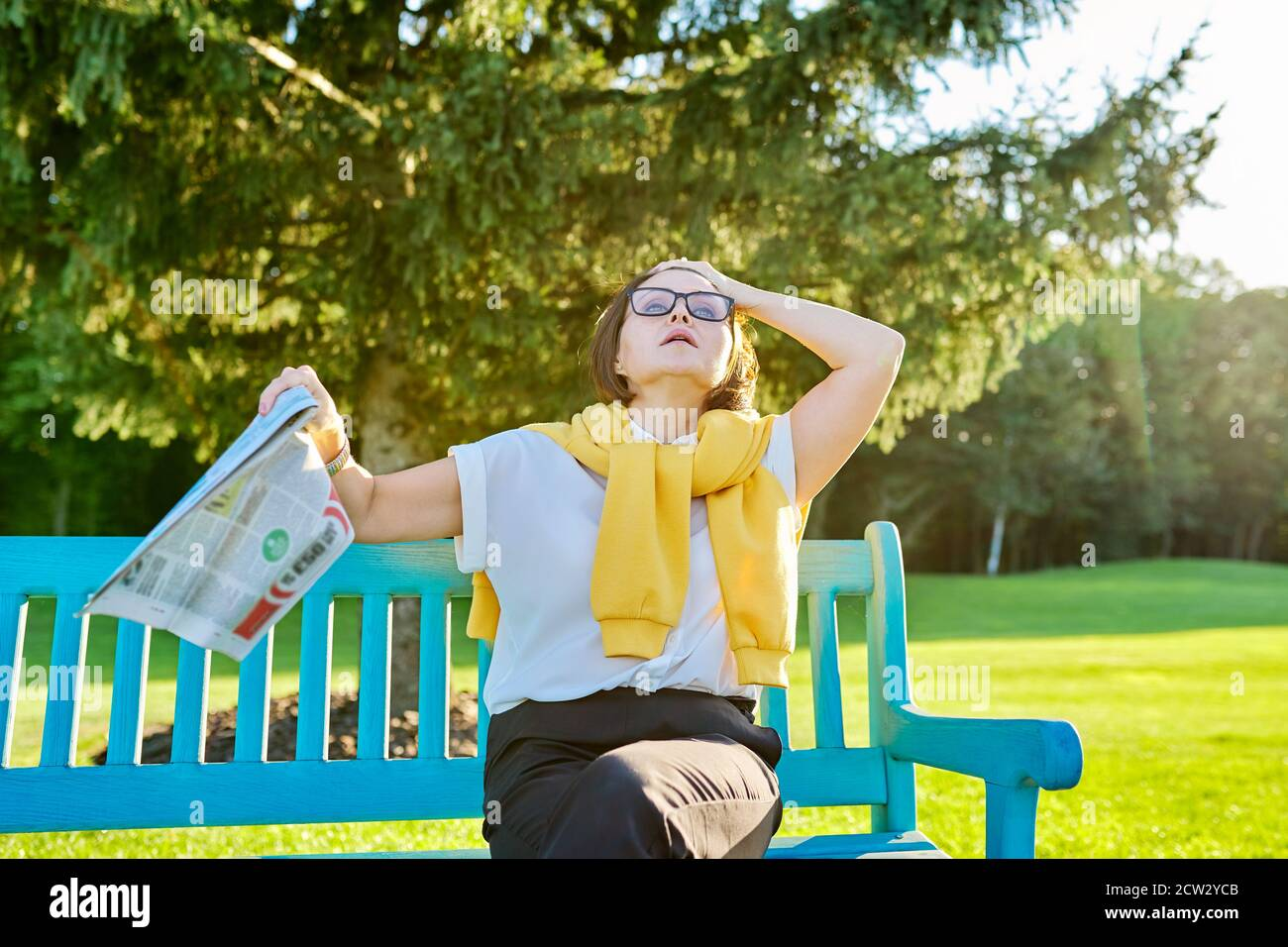 Symptoms of menopause in mature woman, female waves newspaper to cool off Stock Photo