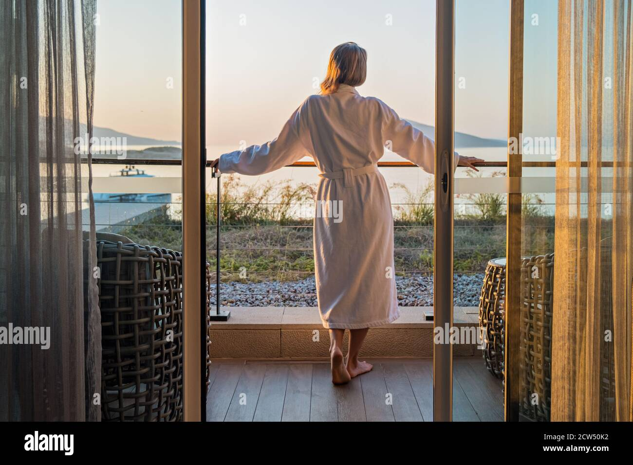 Beautiful woman from back in bathrobe on terrace of hotel room with Sea View Stock Photo