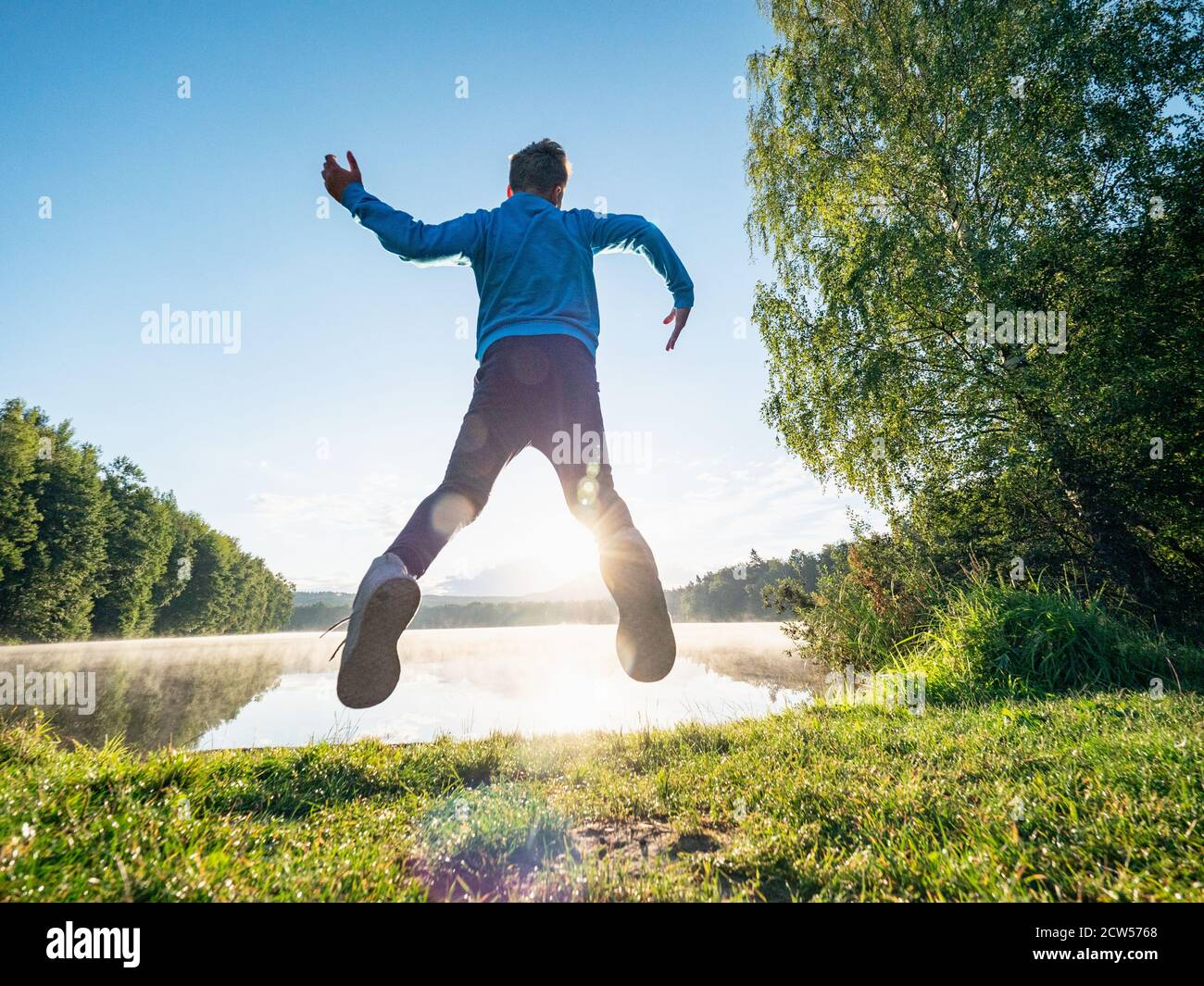 Crazy jumping boy celebrate freedom and make a fun at lake. Crazy and amazing  childood Stock Photo