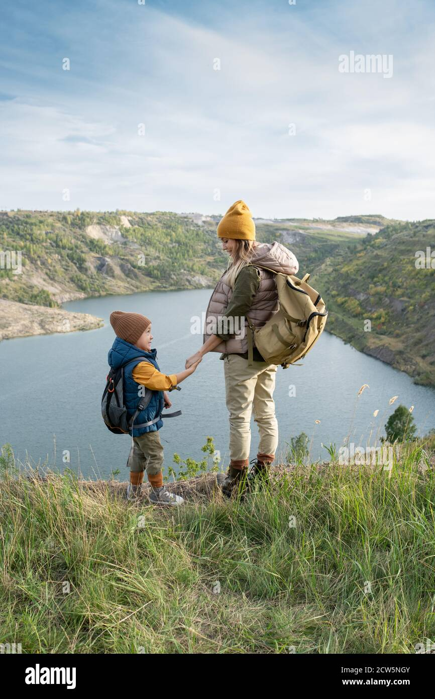 Back view of young mother and little son with backpacks looking at each other Stock Photo