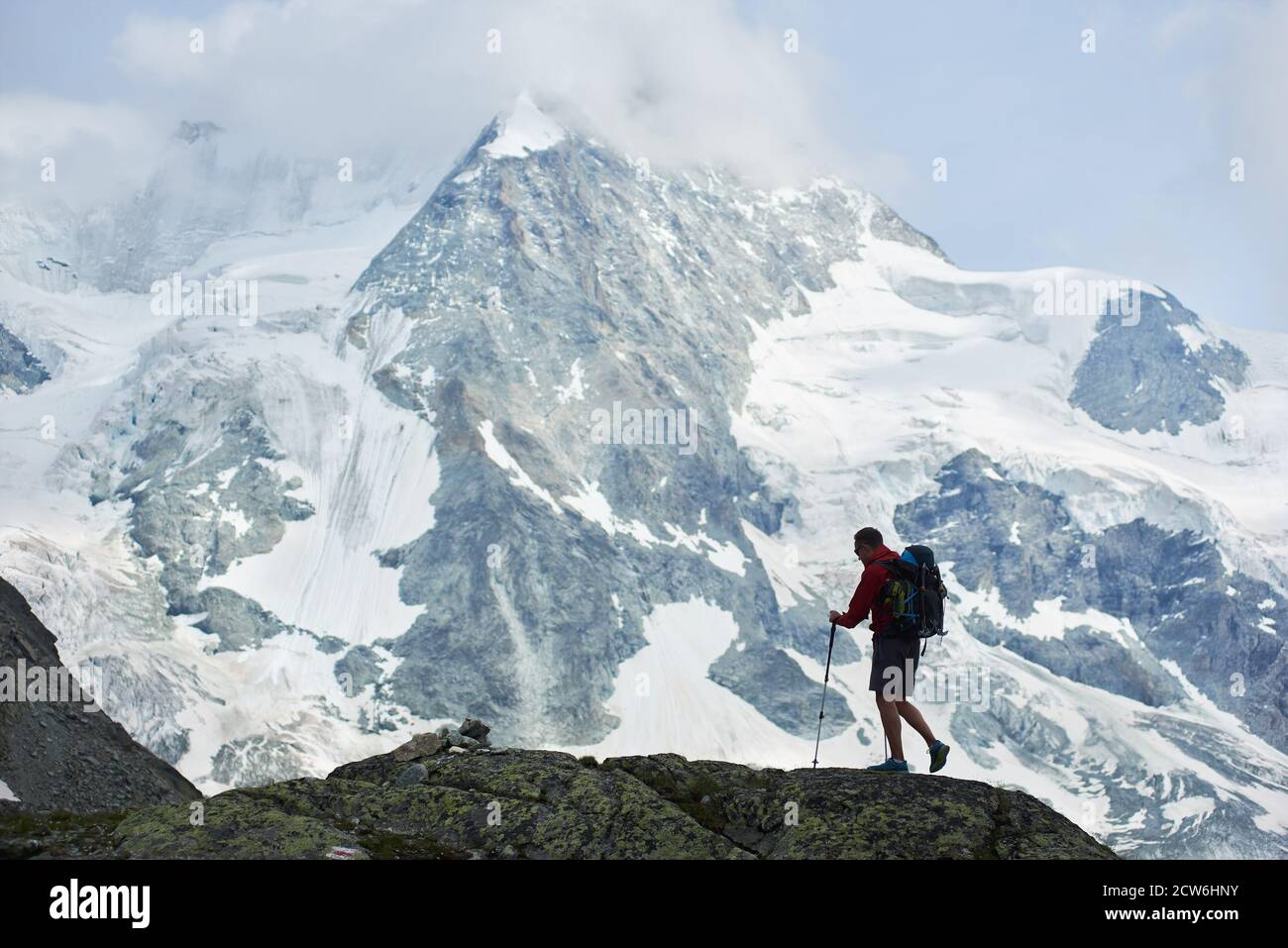Male tourist with backpack walking using trekking sticks. Amazing, rocky mountain Ober Gabelhorn in snow in the Pennine Alps in Switzerland on background. Concept of tourism, hiking, alpinism Stock Photo