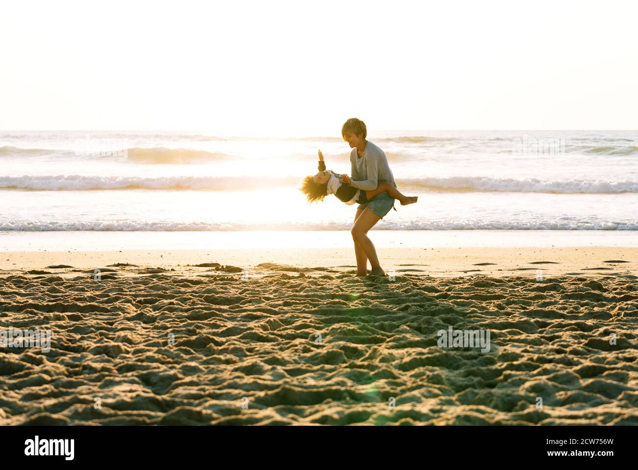 Child spinning in the arms his mother very happily on a sunset at the beach Stock Photo