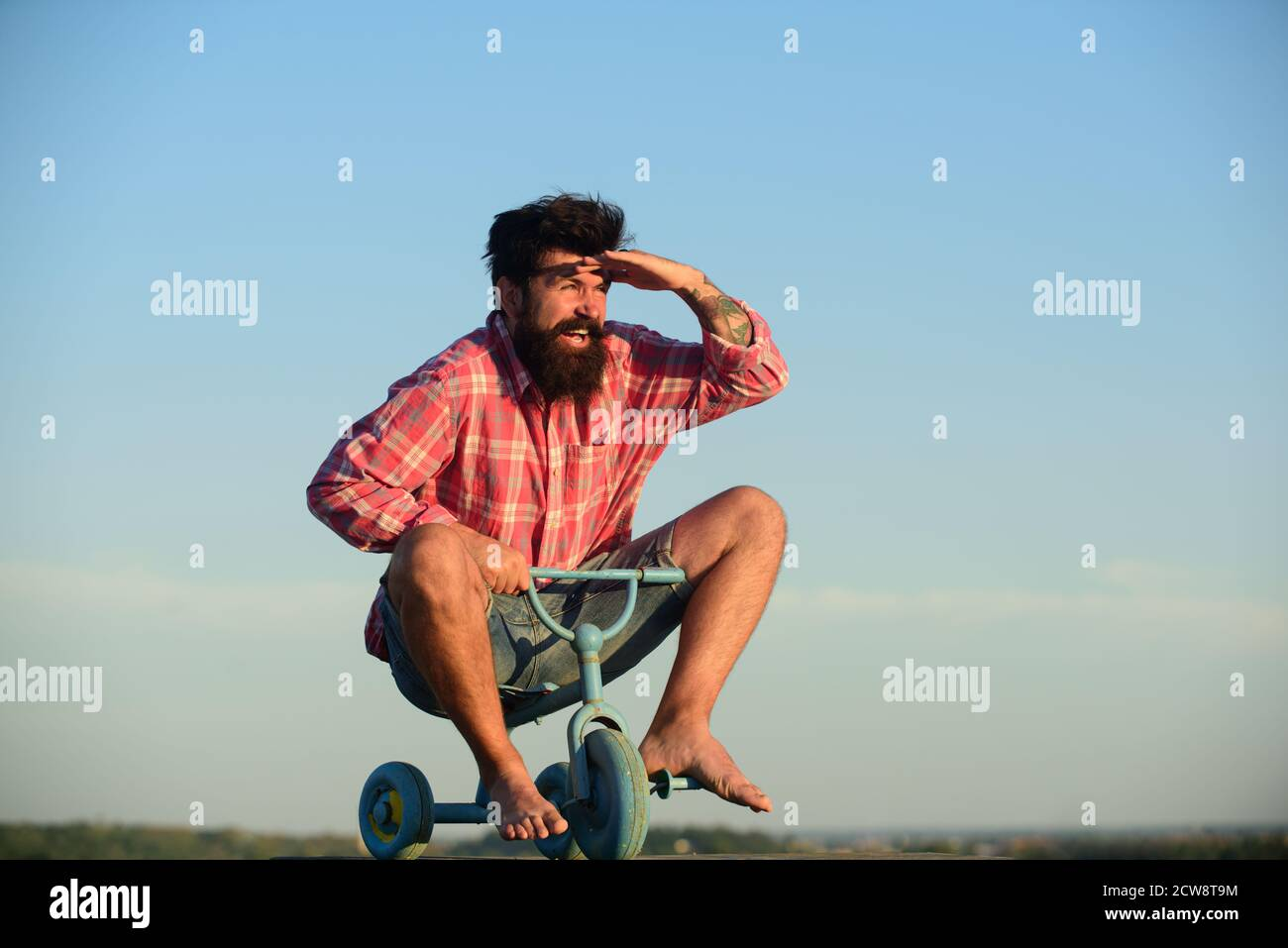 Crazy man riding a small bicycle. Funny man on a childrens bike. Stock Photo