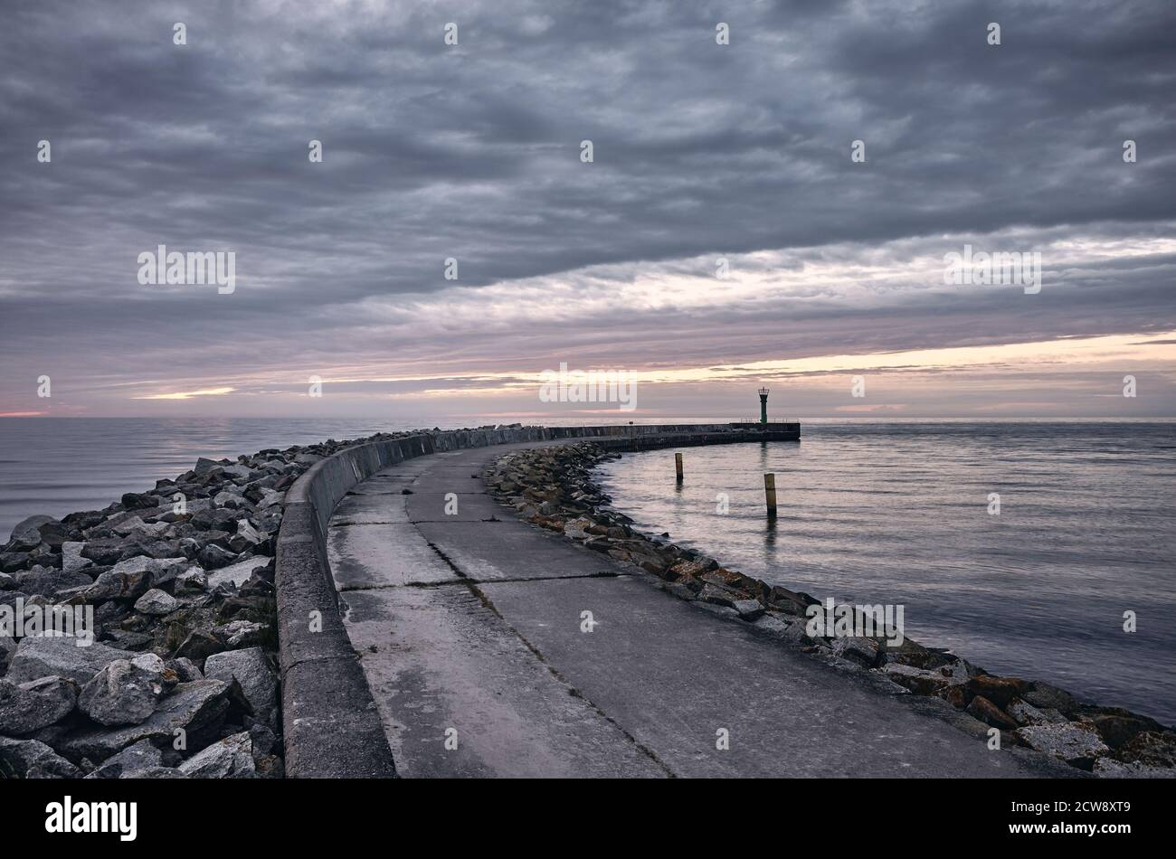 Rocky pier at sunset with dark sky, color toning applied. Stock Photo