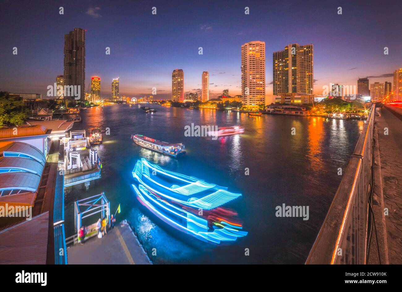 Skyscrapers and Light Trails of Traffic on the Chao Phraya River in Bangkok, Thailand as Seen from Taksin Bridge at Might Stock Photo