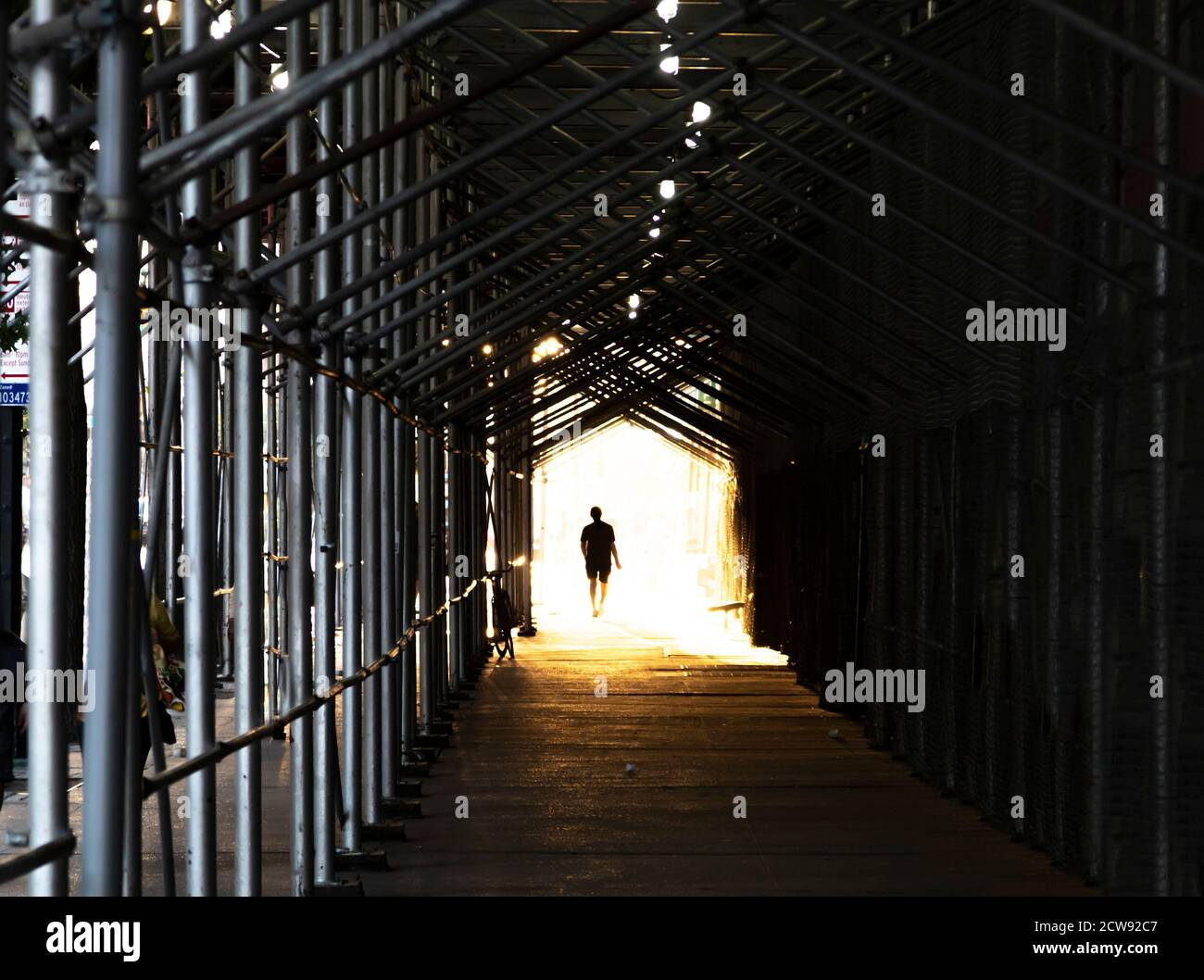 Man walking down the city sidewalk under construction scaffolding with a bright light glowing in the background Stock Photo