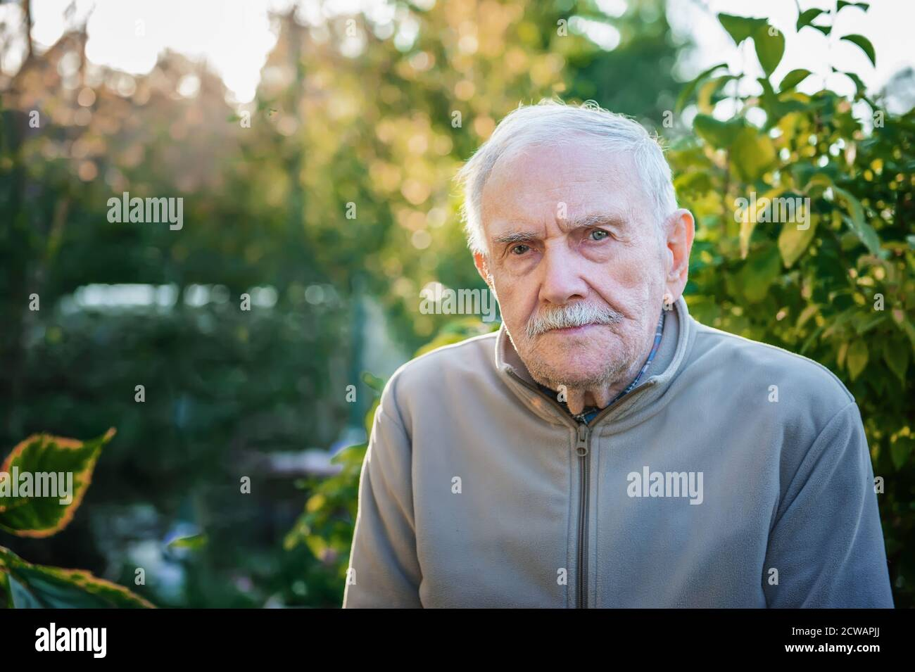 Artistic portrait of a friendly older old man on the street close-up. Copy space Stock Photo