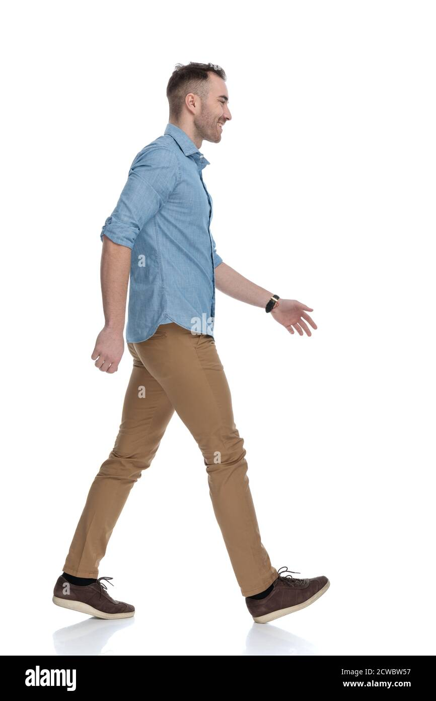 Side view of happy casual man laughing and wearing blue shirt, stepping on white studio background Stock Photo