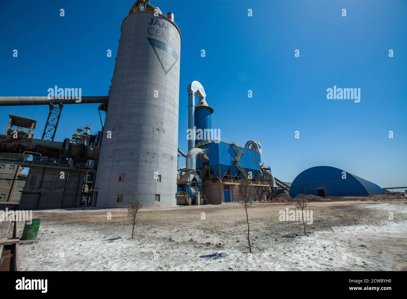 Mynaral/Kazakhstan - April 23 2012: Jambyl Cement plant. Factory buildings and silos. Panorama view with wide-angle lens. Blue sky. Stock Photo