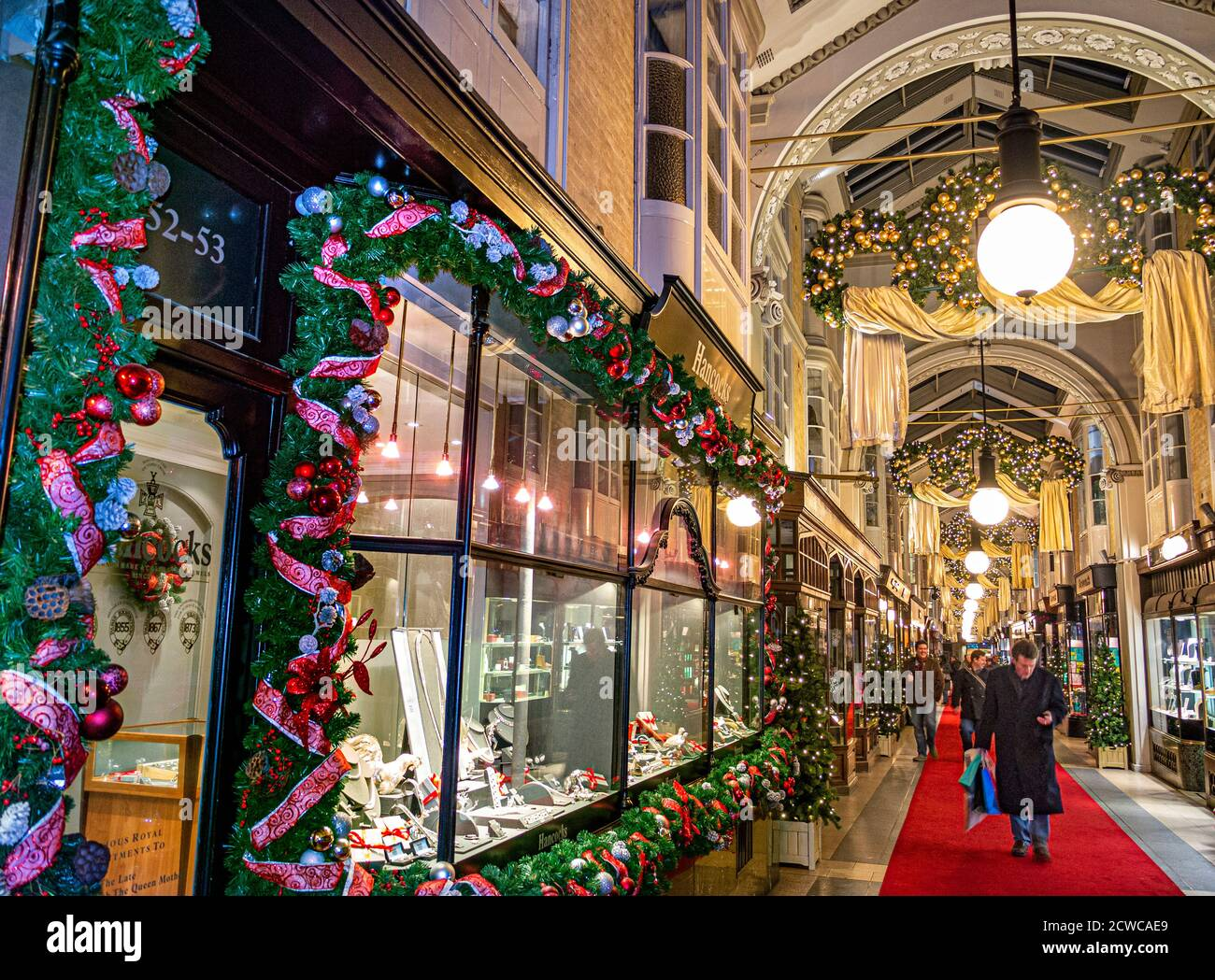 LONDON CHRISTMAS Burlington shopping arcade in Piccadilly with traditional Christmas festive decorations and Christmas shoppers shopping in covered luxury retail interior environment London UK Stock Photo