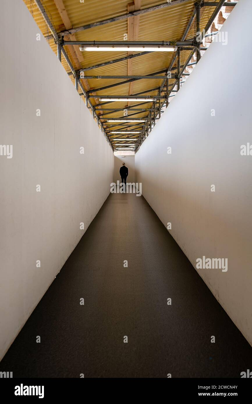 Man walking down a corridor towards a well lit end exit Stock Photo