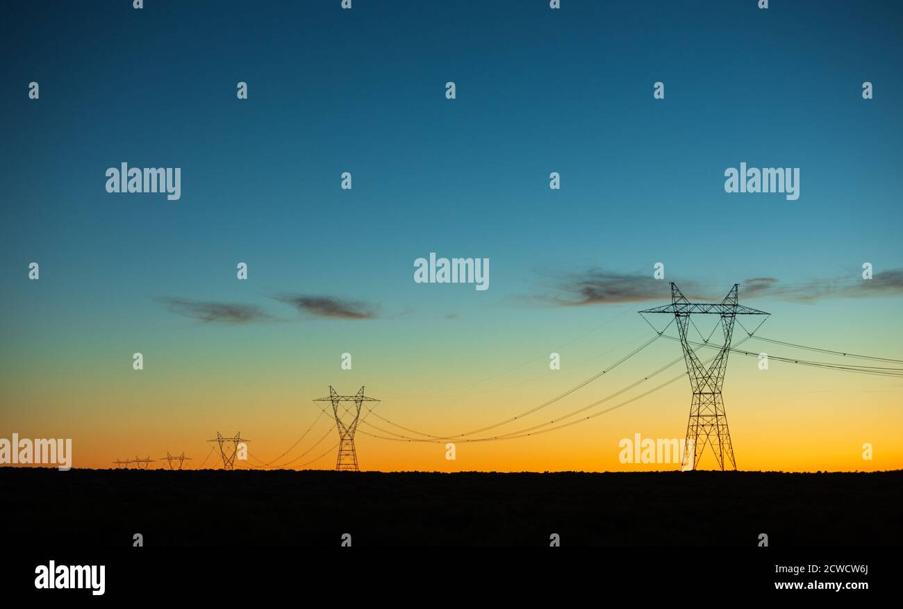 power lines being lit up in the dusk sky Stock Photo