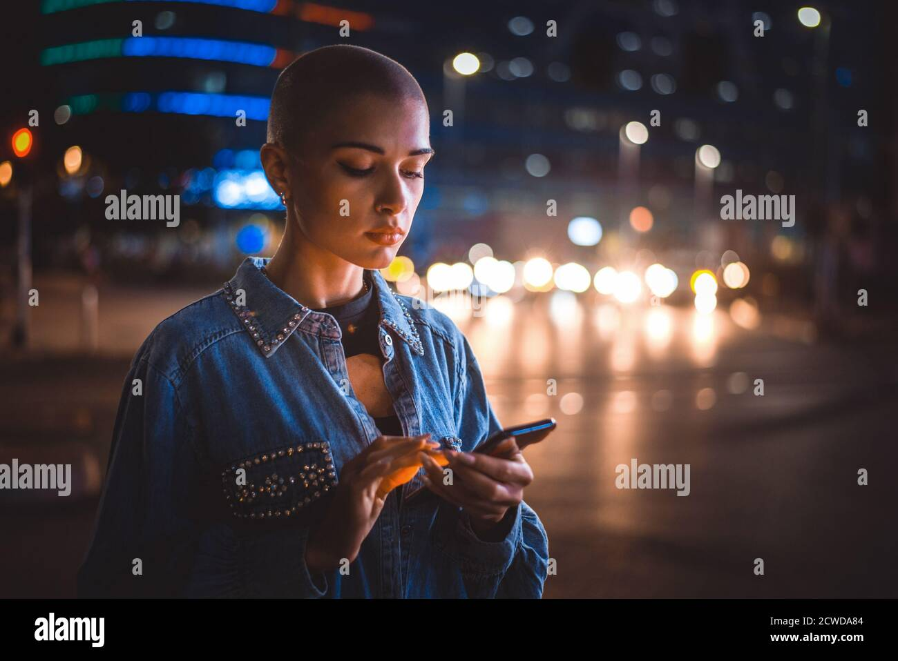 Image of a young woman using mobile phone on the street. Girl with short shaved hair walking in the evening in the city center Stock Photo
