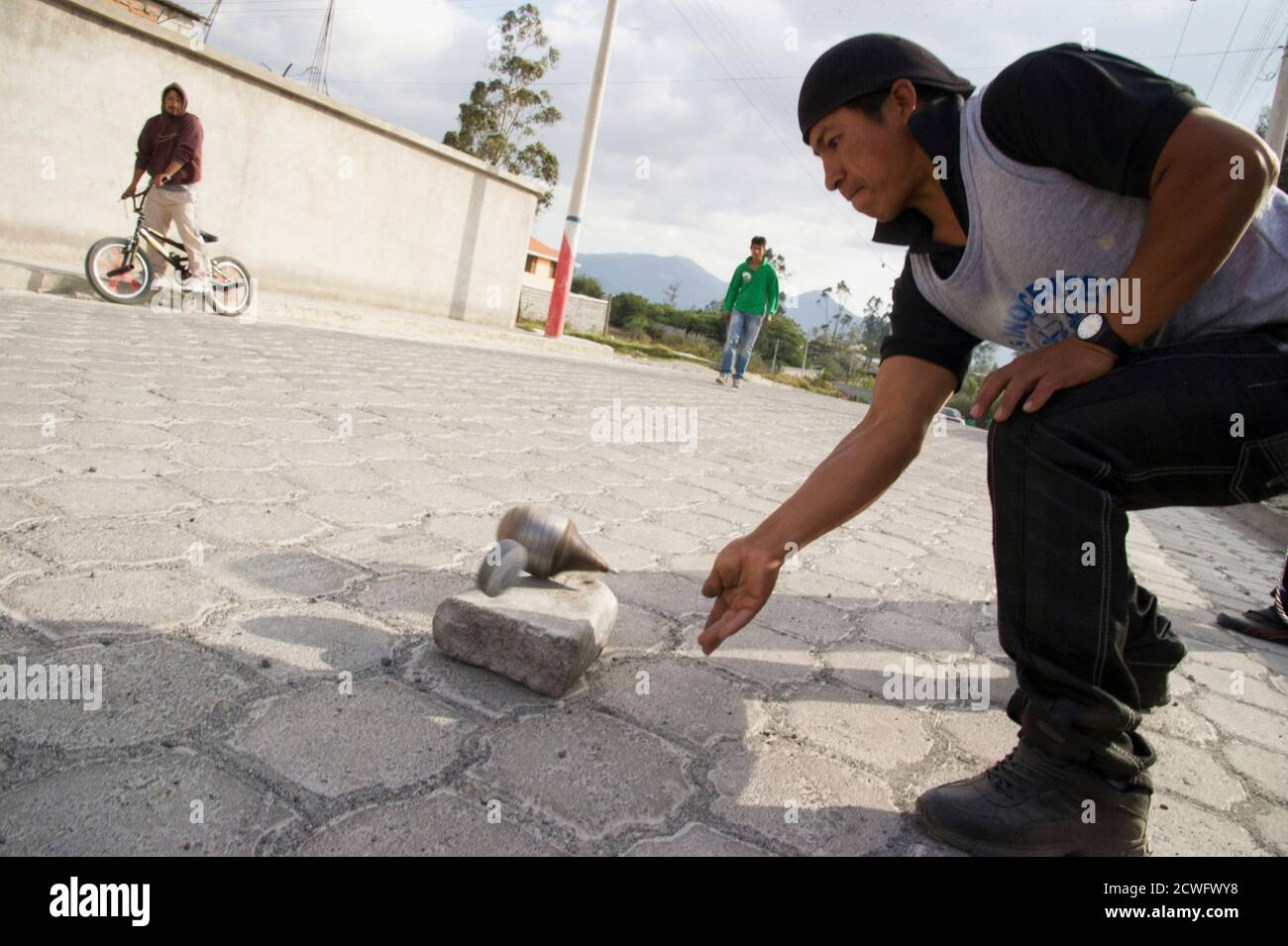 """A resident hits his """"trompo gigante"""" to play a """"cave"""" during a game of """"trompo gigante"""" in Cotacachi, about 120 km (75 miles) north of Quito September 8, 2012. Fifteen teams, each made up of 10 members, representing different neighbourhoods of the village compete to see who can hit """"la bola"""" from the start point in the main park to the finishing point about 8-10 km (5-6.2 miles) away through the streets of Cotacachi with the least number of """"caves"""", or hits. The game, an annual event, runs from August to November and was started in the village famous for its leather 17 years ago. The contestan Stock Photo"""