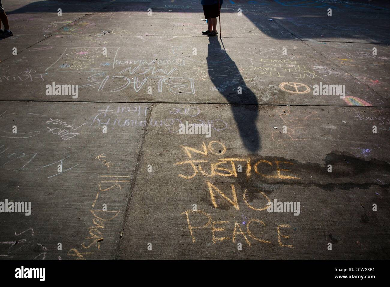 A man with a walking stick passes protest messages written in a parking lot before the announcement of the name of the officer involved in the shooting of Michael Brown in Ferguson, Missouri August 15, 2014. Police Chief Thomas Jackson on Friday identified Darren Wilson as the police officer who fatally shoot an unarmed black teenager, which led to days of sometimes-violent demonstrations. Jackson announced the name at a press conference held near a QuikTrip convenience store that had been burned amid protests over the shooting of Brown, 18, last Saturday.  REUTERS/Lucas Jackson (UNITED STATES Stock Photo