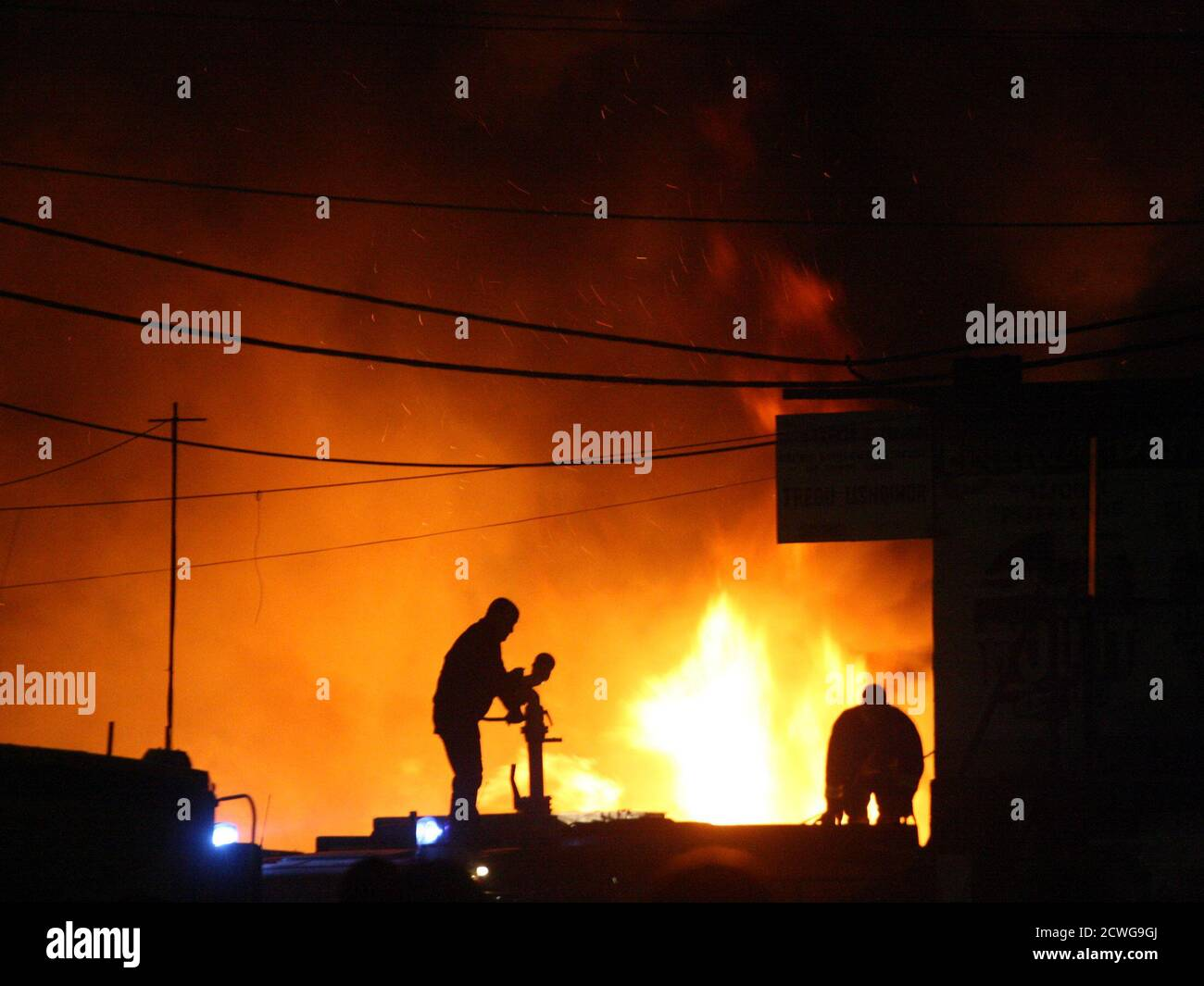 Two Albanian firefighters try to put out a huge fire, which started at a fireworks warehouse in Tirana November 21, 2011. Some shops and warehouses nearby burnt to the ground, but there were no deaths or injuries, according to a police spokesman.   REUTERS/Arben Celi (ALBANIA - Tags: DISASTER TPX IMAGES OF THE DAY) Stock Photo