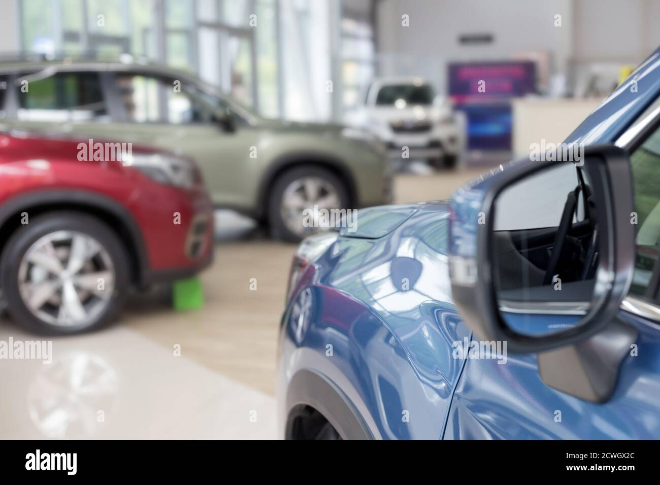 New cars at dealer showroom. Themed blur background with bokeh effect. Car auto dealership. Prestigious vehicles. Stock Photo