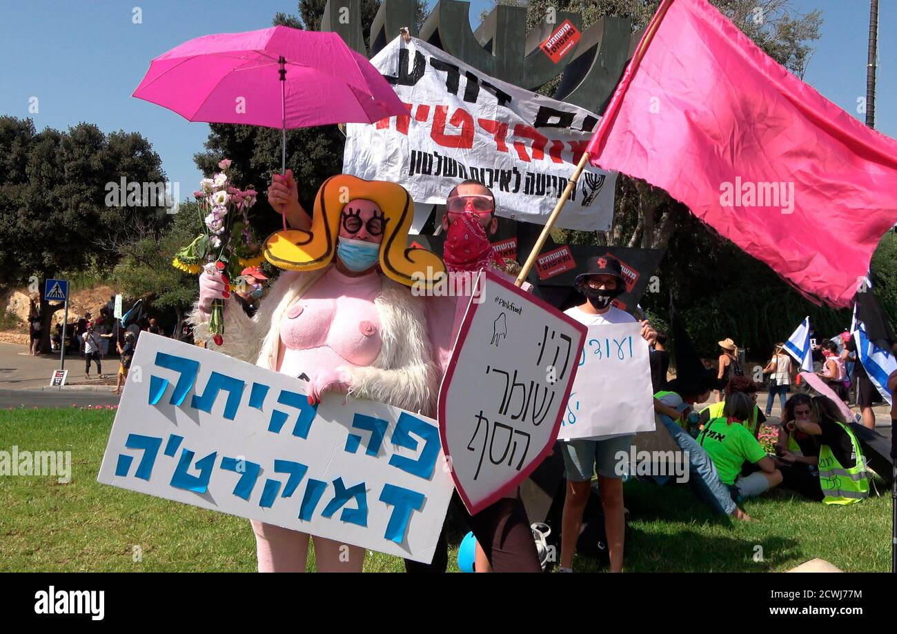 """JERUSALEM, ISRAEL - SEPTEMBER 29: A protester dressed in a busty cartoon costume holds a placard which reads """"Democracy was here"""" in front of the Israeli parliament during a demonstration over legislation restricting protests amid a nationwide lockdown aimed at curbing the coronavirus pandemic on September 29, 2020 in Jerusalem, Israel. The Israeli parliament approved changes to the Coronavirus Law that would limit protests against Prime Minister Benjamin Netanyahu demanding his resignation over his indictment on corruption charges and handling of the coronavirus pandemic. Stock Photo"""