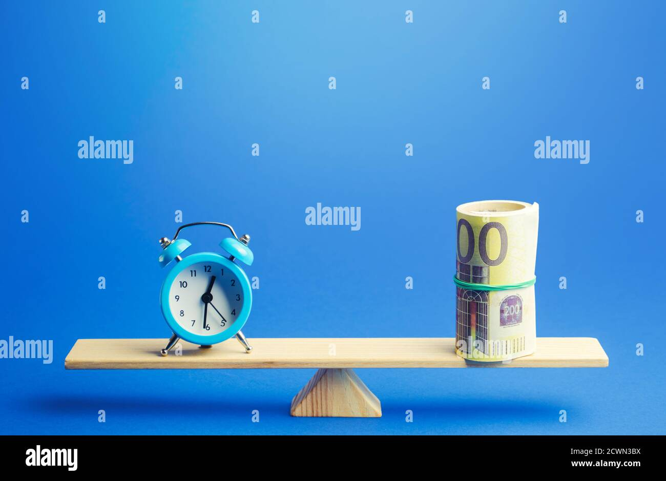 Blue alarm clock and a bundle of euro on scales. Fair hourly wages. Profitability and return on investment. Rental. Balance between life and career. T Stock Photo