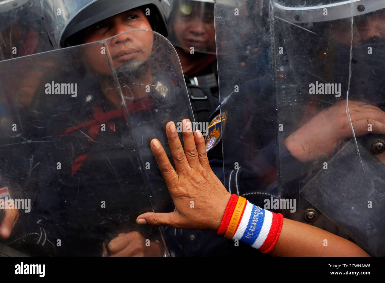 An anti-government protester pushes against riot policemen at a barricade near the Government House in central Bangkok February 14, 2014. Thousands of Thai riot police were deployed on Friday to seize back protest sites around government buildings in Bangkok that have been occupied for months by demonstrators seeking to topple Prime Minister Yingluck Shinawatra.  REUTERS/Damir Sagolj (THAILAND - Tags: SOCIETY CIVIL UNREST) Stock Photo