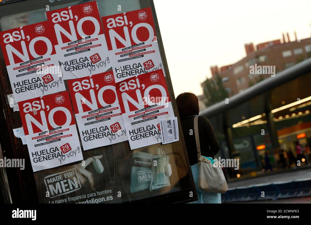 A woman waits at a bus shelter at rush hour during a nationwide general strike in Madrid September 29, 2010. Spanish labour groups, including the two largest unions CCOO and UGT, have called the first general strike in eight years to protest against spending cuts the government says are needed to allay concerns the country could slide into a debt crisis that would threaten the unified euro currency. Banners read 'Not that way (related to the government), general strike, I'm going!'.  REUTERS/Sergio Perez (SPAIN - Tags: CIVIL UNREST BUSINESS EMPLOYMENT) Stock Photo