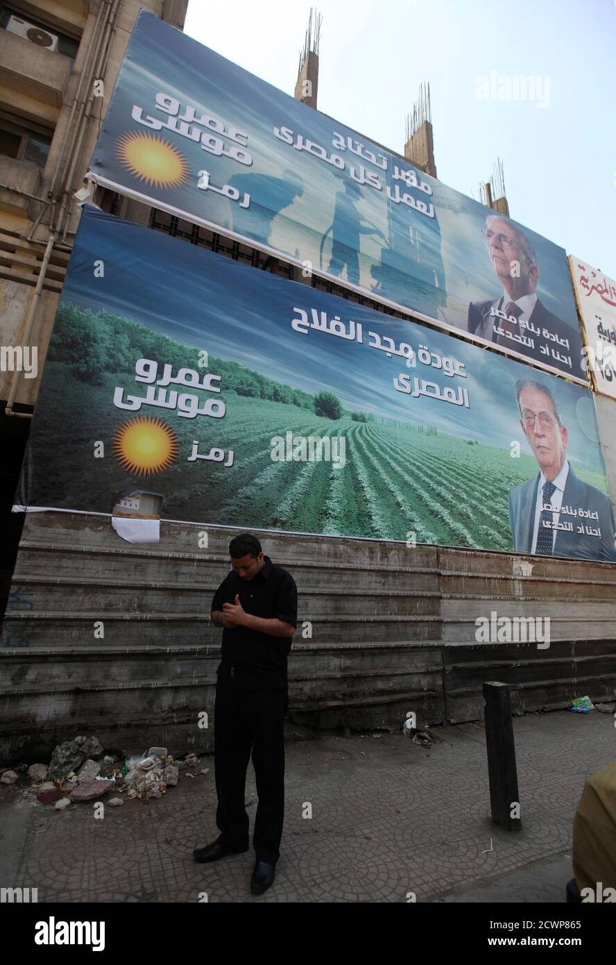 """A man looks at his mobile phone below campaign election billboards of presidential candidate and former Arab League secretary general Amr Moussa in Cairo, May 7, 2012. Voting starts on May 23-24 in the election to choose a new president after Hosni Mubarak was turfed out of office last year. The billboard reads, """"Amr Moussa, we are up to the challenge."""" REUTERS/Amr Abdallah Dalsh  (EGYPT - Tags: POLITICS ELECTIONS) Stock Photo"""