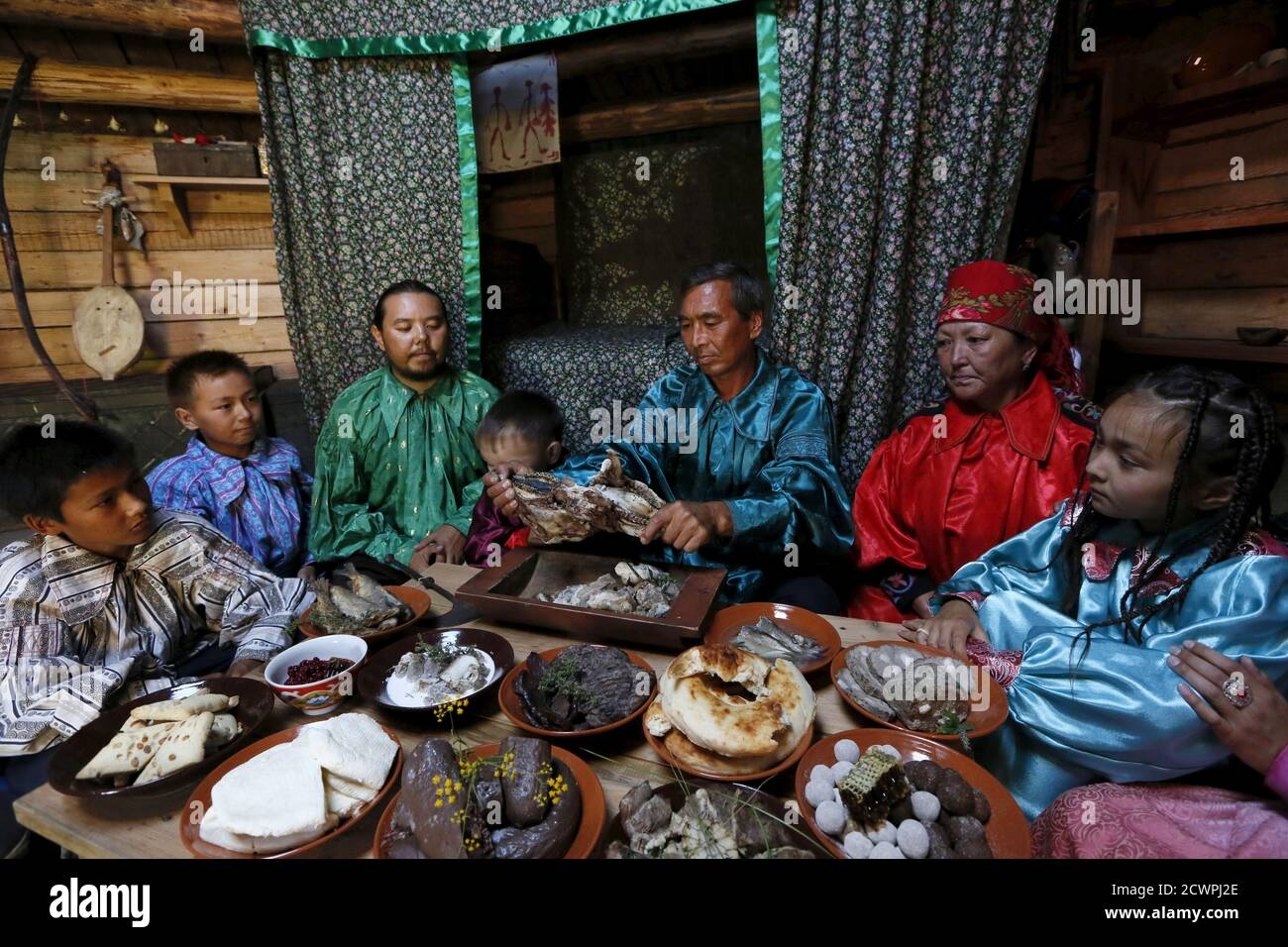 "Members of national folklore and ethnographic groups and employees of a museum-preserve participate in the reconstruction of daily life and traditional holidays celebrated by indigenous population of the Republic of Khakassia during a demonstration for visitors inside a traditional wooden yurt near Kazanovka village, southwest of the city of Abakan, Russia, July 24, 2015. The ""Khakas aal"" (Khakas settlement) ethnographic complex demonstrates the model of a traditional local settlement of the 19th century based on local traditional wooden yurts. The museum preserve is located in a picturesque f Stock Photo"