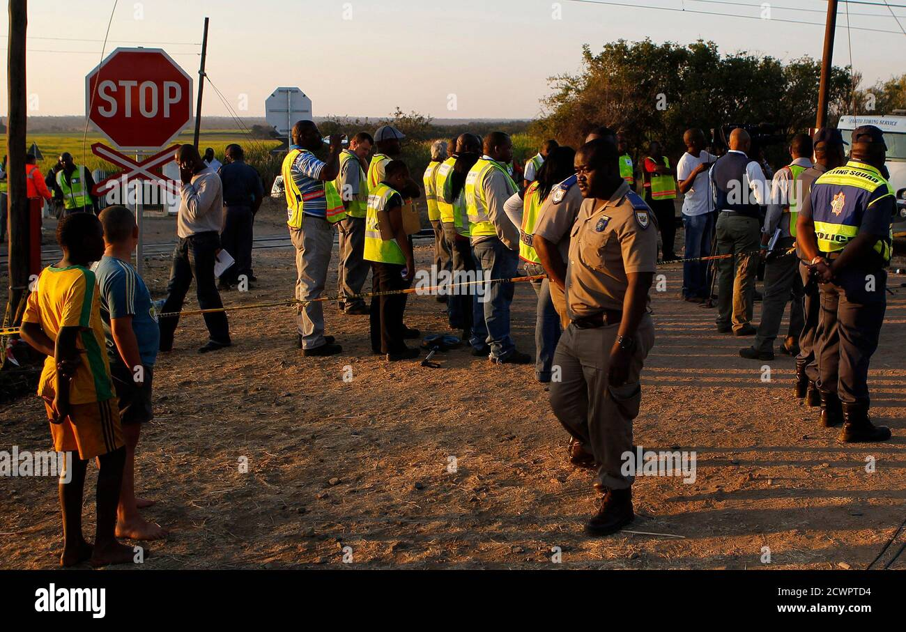 Emergency workers and locals gather at a scene of a collision between a train and a truck in the eastern Mapumalanga province, between the city of Nelspruit and the Mozambique border, July 13, 2012. A South African train carrying coal for export to Mozambique smashed into a truck on Friday but there was no derailment, the state rail operator said. At least 19 people were killed and 24 injured in the collision, local emergency services reported. REUTERS/Siphiwe Sibeko (SOUTH AFRICA - Tags: TRANSPORT DISASTER) Stock Photo