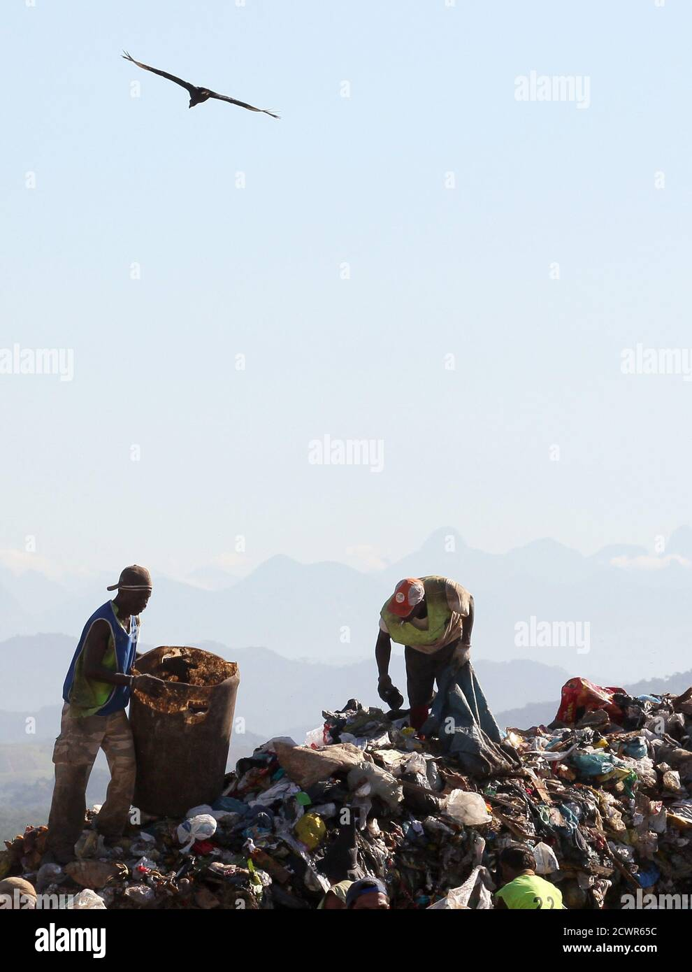 """Men collect recyclable materials from Jardim Gramacho landfill, one of the world's largest garbage dumps, where the documentary """"Lixo Extraordinario"""" (Waste Land) was filmed, in Rio de Janeiro January 28, 2011. Waste Land follows artist Vik Muniz on a journey from his home in Brooklyn to his native Brazil, where he met a band of garbage pickers in the world's largest garbage dump, Jardim Gramacho. Waste Land has been nominated for an Oscar in the category of Best Documentary. REUTERS/Sergio Moraes (BRAZIL - Tags: ENVIRONMENT SOCIETY) Stock Photo"""