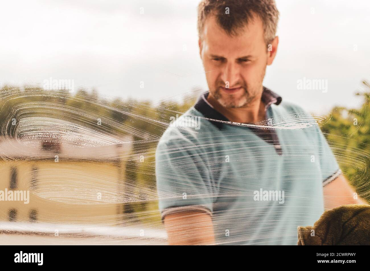 A middle aged man cleaning window with a rag and a window cleaner Stock Photo