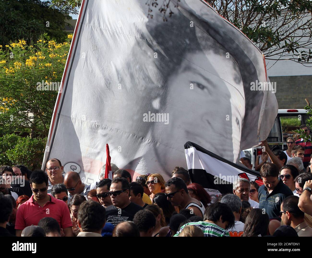 People attend the funeral of Brazil's 1982 World Cup captain Socrates in Ribeirao Preto December 4, 2011. Socrates, the 'Golden Heel' renowned as one of the great playmakers of his generation, died in hospital on Sunday of septic shock at the age of 57, his doctors said in a statement. REUTERS/Paulo Whitaker (BRAZIL - Tags: SPORT SOCCER OBITUARY) Stock Photo