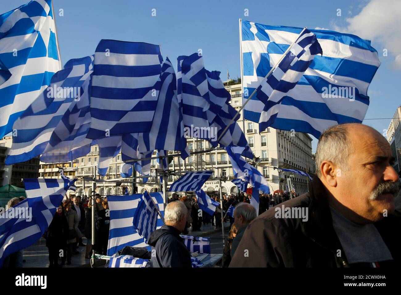 """Greek national flags displayed for sale flutter during an anti-austerity pro-government demonstration in front of the parliament in Athens February 15, 2015. Greece has agreed with its European partners that there needs to be a """"national reform plan"""" to deal with decades-long issues of the economy, its government spokesman said on Sunday. Greece and its euro zone partners are in difficult negotiations over demands by the new government of leftist Prime Minister Alexis Tsipras for an end to austerity and a renegotiation of Greece's debt.   REUTERS/Yannis Behrakis  (GREECE - Tags: POLITICS BUSIN Stock Photo"""