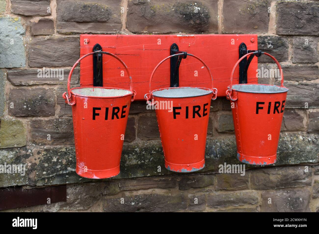 close up of 3 red Fire buckets hanging from hooks on a stone wall outside Stock Photo