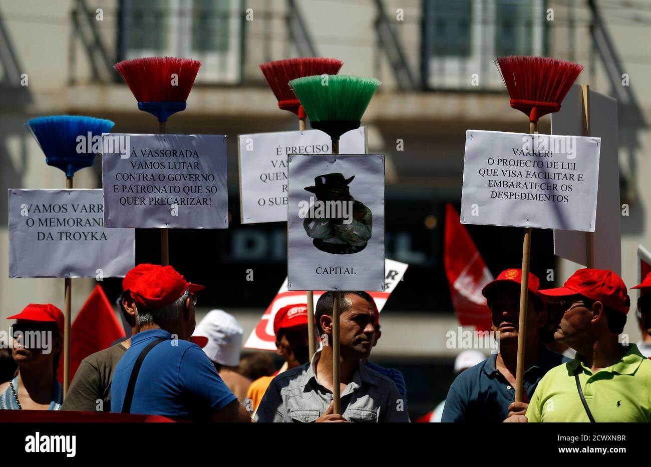 "Demonstrators hold up brooms with placards during a rally in Lisbon July 28, 2011. Union activists were protesting against changes in labor legislation. The placards read: ""We are going to fight against the government because it wants unstable labor!"" (2nd L) and ""Sweep! The law project that tries to cheapen the sackings"" (R). REUTERS/Rafael Marchante (PORTUGAL - Tags: BUSINESS POLITICS CIVIL UNREST IMAGES OF THE DAY) Stock Photo"