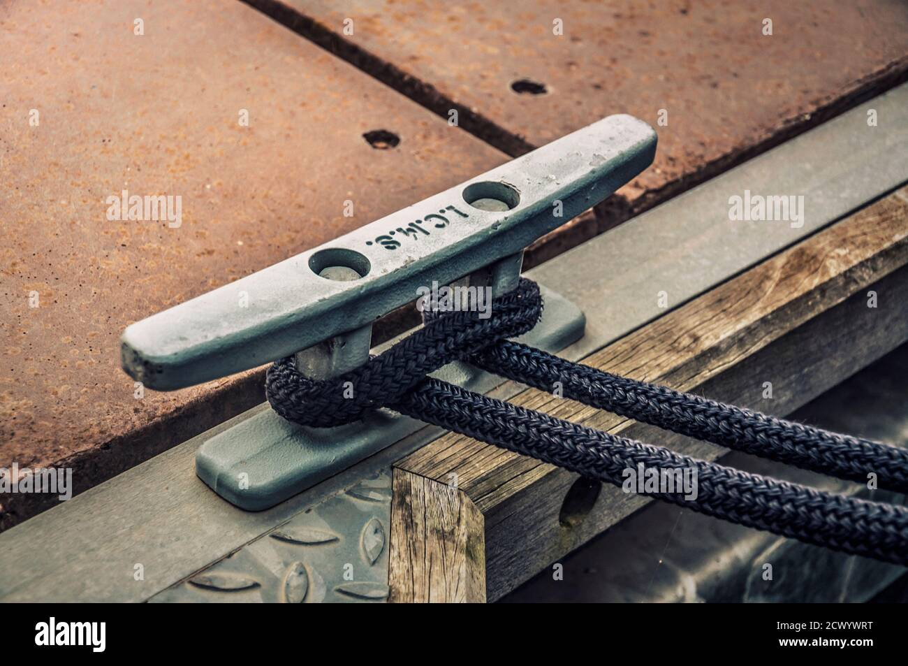 Close up of the dock cleat with a rope tied around it. Connection visual concept as boat tied and linked to the pontoon. Stock Photo