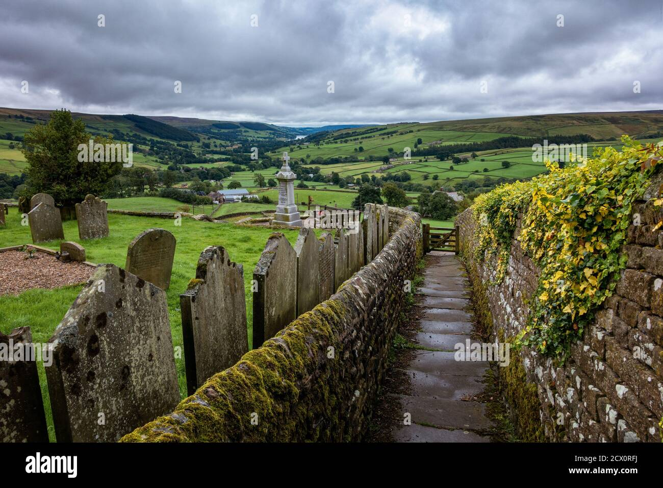 View down a drystone wall & path from Middlesmoor next to the graveyard through Nidderdale towards Pateley Bridge, North Yorkshire, UK Stock Photo