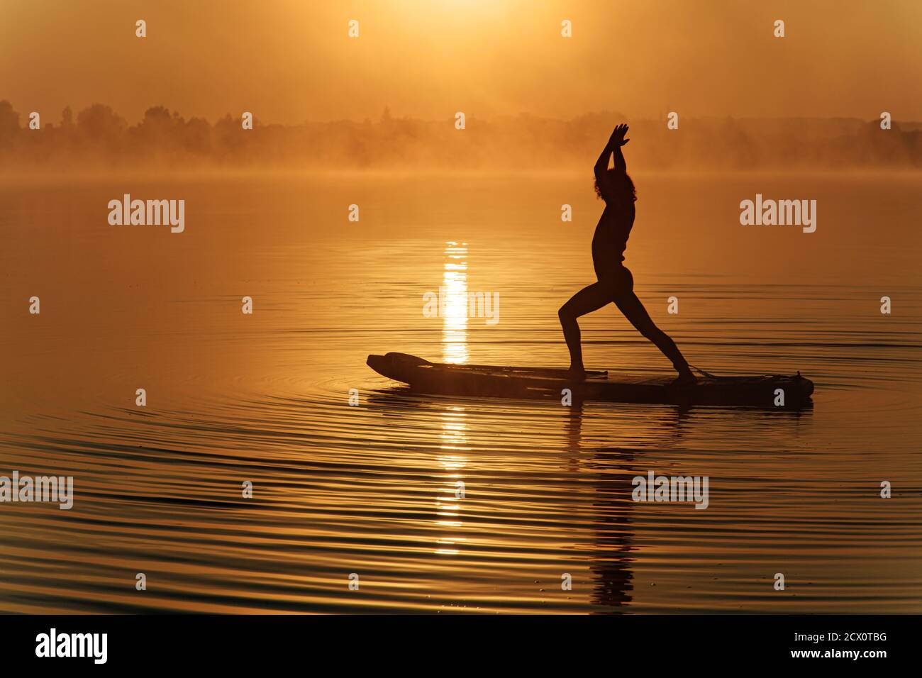 Silhouette of sportive man doing yoga on paddle board Stock Photo