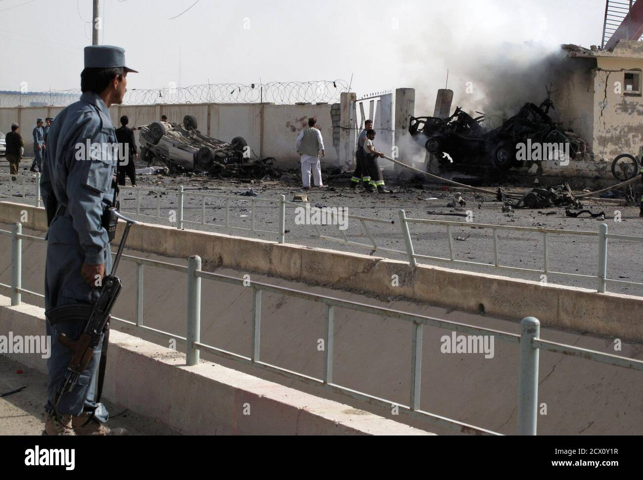 An Afghan policeman (L) watches as firefighters work at the site after a car bomb explosion in Lashkar Gah, capital of Helmand province July 31, 2011. The explosion killed at least six Afghan police in the southern city of Lashkar Gah on Sunday, said a spokesman for the Helmand provincial governor.  REUTERS/Abdul Malik Watanyar (AFGHANISTAN - Tags: CIVIL UNREST IMAGES OF THE DAY) Stock Photo